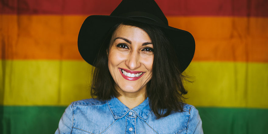 happy woman in front of pride flag